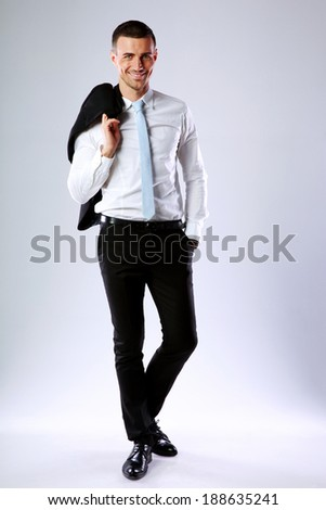 Full length portrait of a happy business man holding jacket on shoulder on gray background - stock photo