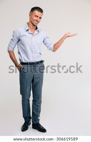 Full length portrait of a happy businessman holding copyspace on the palm over gray background - stock photo