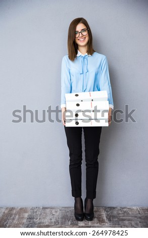 Full length portrait of a happy businesswoman standing with folders. Wearing in blue shirt and glasses. Looking at camera - stock photo
