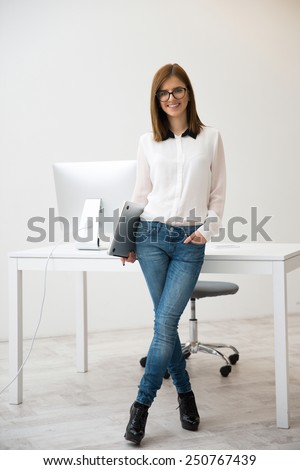 Full length portrait of a happy businesswoman standing with laptop in office - stock photo