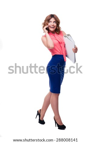 Full length portrait of a happy businesswoman talking on the phone and holding folders isolated on a white background. Looking up - stock photo