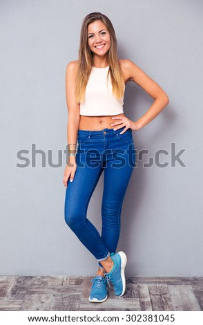 Full length portrait of a happy casual woman standing on gray background. Looking at camera - stock photo