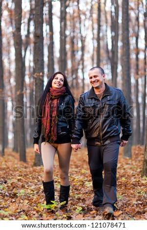 Full length portrait of a happy couple walking in the woods while holding hands - stock photo