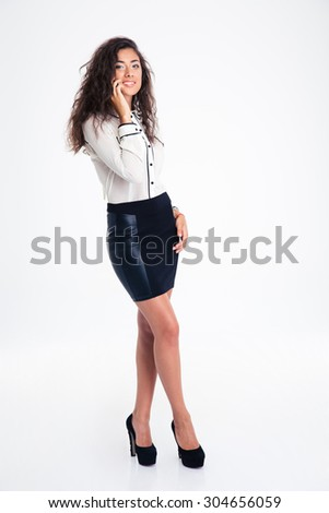 Full length portrait of a happy cute businesswoman talking on the phone isolated on a white background. Looking at camera