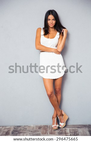 Full length portrait of a happy cute woman in trendy white dress standing in studio - stock photo