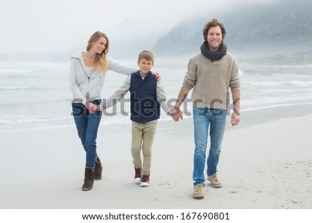 Full length portrait of a happy family of three walking on sand at the beach - stock photo