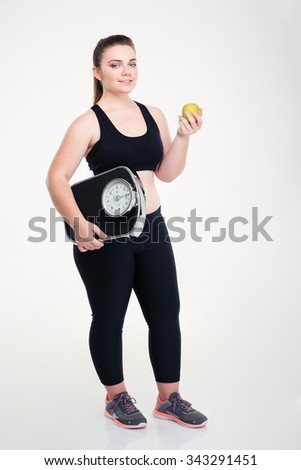 Full length portrait of a happy fat woman holding weighing machine and apple isolated on a white background - stock photo