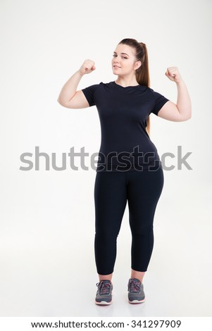 Full length portrait of a happy fat woman showing her biceps isolated on a white background - stock photo