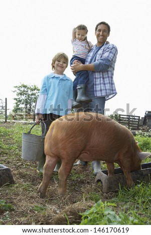 Full length portrait of a happy father and children with pig in sty against clear sky - stock photo