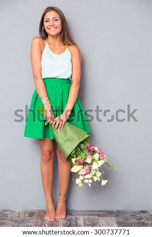 Full length portrait of a happy girl holding bouquet with flowers on gray background - stock photo