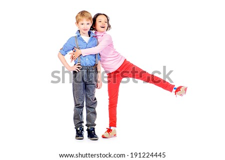 Full length portrait of a happy little girl embracing a cute boy. Children. Isolated over white.