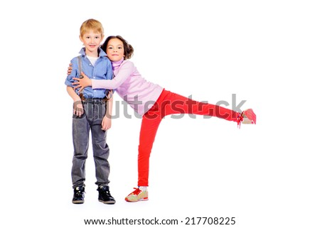 Full length portrait of a happy little girl embracing a cute boy. Children. Isolated over white. - stock photo