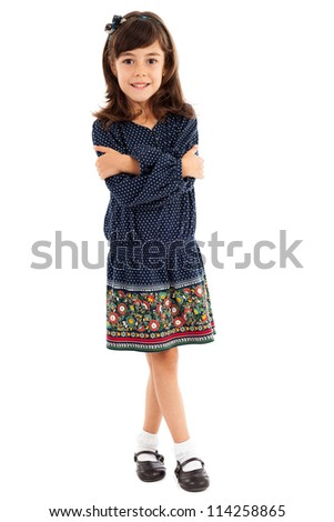 Full length portrait of a happy little girl with crossed legs and arms isolated on white