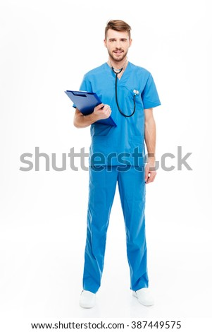 Full length portrait of a happy male doctor standing with clipboard isolated on a white background - stock photo