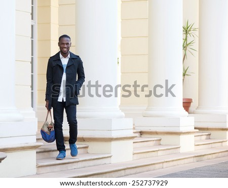 Full length portrait of a happy man walking outside hotel with bag - stock photo