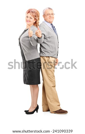 Full length portrait of a happy mature couple giving thumbs up isolated on white background - stock photo
