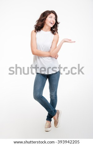 Full length portrait of a happy thoughtful woman holding copyspace on the palm isolated on a white background - stock photo