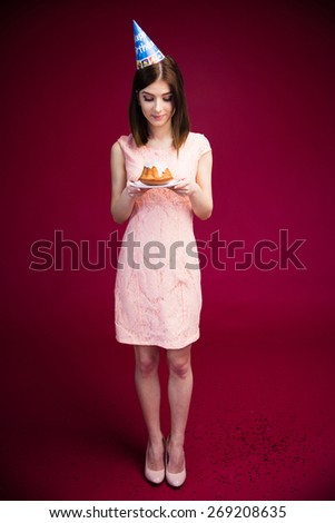 Full length portrait of a happy woman holding cake with candles over pink background. Wearing in dress - stock photo