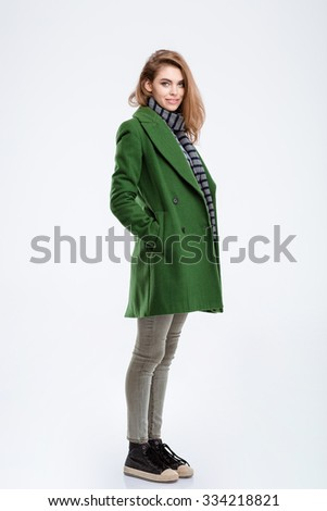 Full length portrait of a happy woman in coat standing isolated on a white background and looking at camera - stock photo