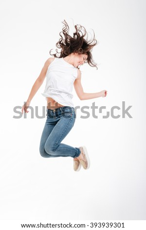 Full length portrait of a happy woman jumping isolated on a white background - stock photo