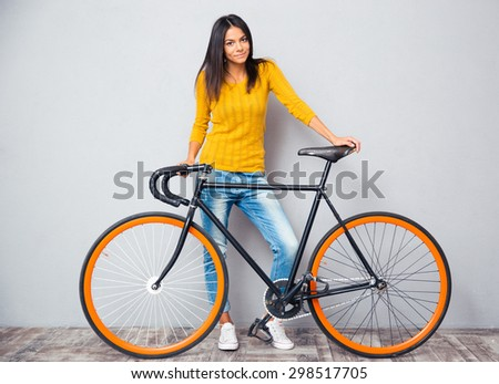 Full length portrait of a happy woman standing near bicycle on gray background. Looking at camera - stock photo