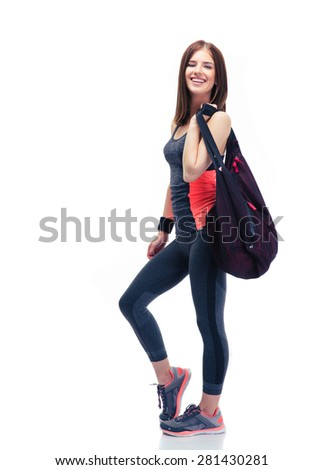 Full length portrait of a happy woman standing with sports bag isolated on a white background. Looking at camera - stock photo