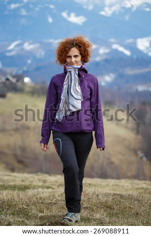 Full length portrait of a happy woman walking on the mountains - stock photo