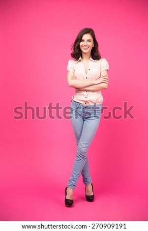 Full length portrait of a happy woman with arms folded standing over pink background. Looking at camera. Wearing in jeans and shirt - stock photo