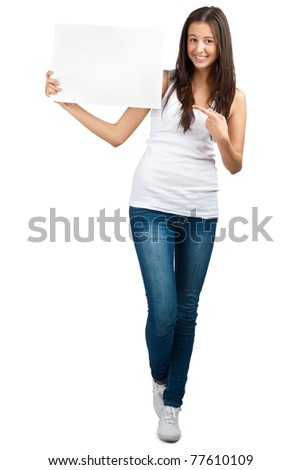 Full length portrait of a happy young casual woman standing and holding a blank signboard, isolated on white background
