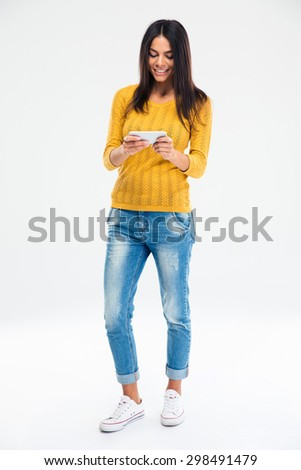 Full length portrait of a happy young girl using smartphone isolated on a white background - stock photo