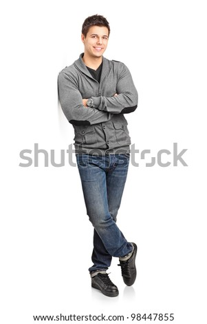 Full length portrait of a happy young man leaning against wall isolated on white background - stock photo