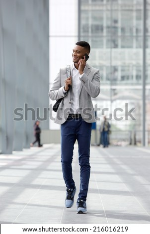 Full length portrait of a happy young man walking and talking on mobile phone - stock photo