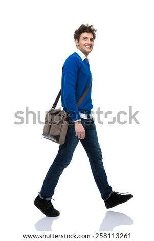 Full length portrait of a happy young man walking over white background - stock photo