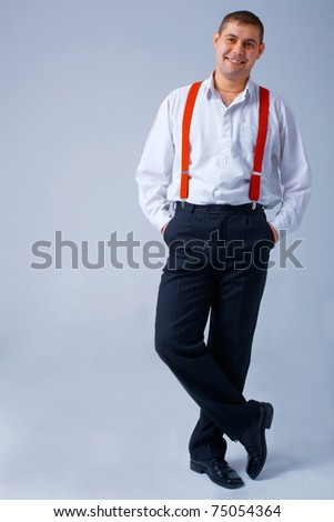 Full length portrait of a happy young man with red braces. - stock photo