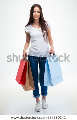 Full length portrait of a happy young woman holding shopping bags isolated on a white background - stock photo