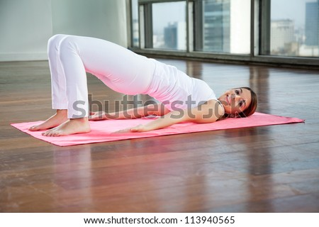Full length portrait of a happy young woman in Bridge pose on yoga mat