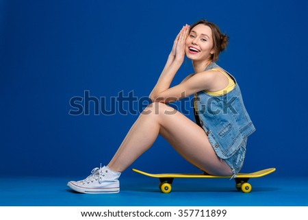 Full length portrait of a happy young woman sitting on skateboard over blue background - stock photo