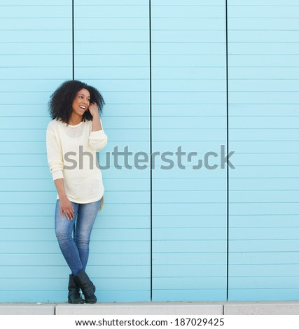 Full length portrait of a happy young woman smiling outdoors against blue background - stock photo