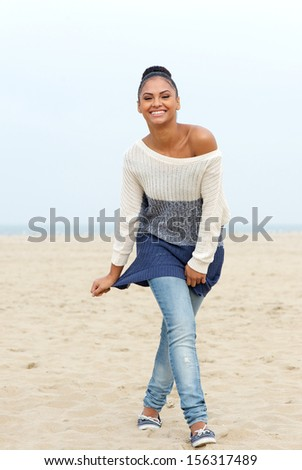 Full length portrait of a happy young woman walking on beach in jeans and sweater - stock photo