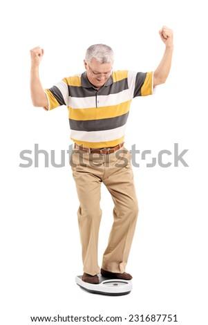 Full length portrait of a joyful senior measuring his weight isolated on white background - stock photo