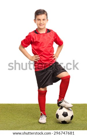 Full length portrait of a junior soccer player stepping over a soccer ball and looking at the camera isolated on white background - stock photo