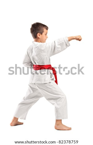 Full length portrait of a karate child posing isolated against white background