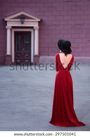 Full length portrait of a lady in long red dress, back view - stock photo