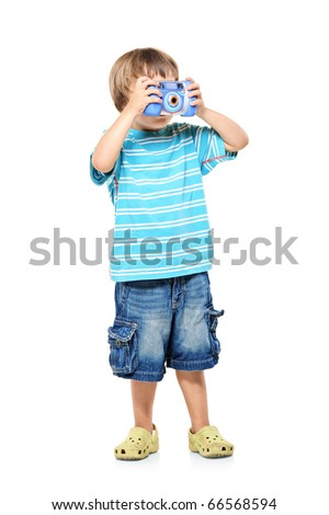 Full length portrait of a little boy taking pictures with a camera isolated against white background - stock photo