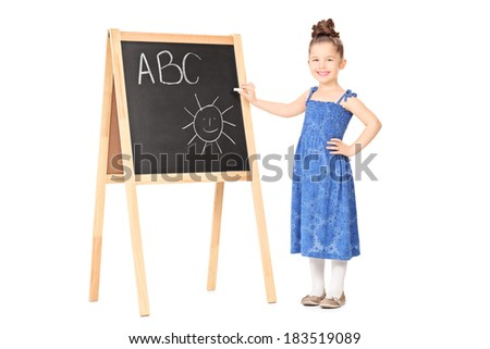 Full length portrait of a little girl writing on a blackboard isolated on white background - stock photo