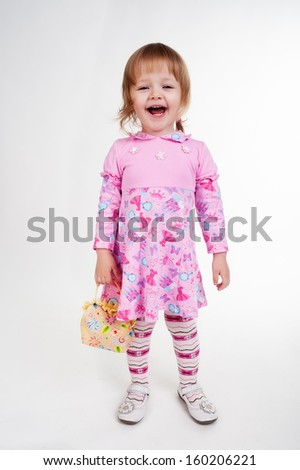 Full length portrait of a little 2 years old girl standing with handbag over white background - stock photo