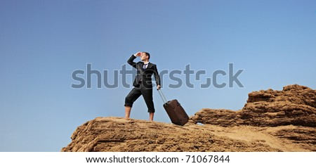 Full length portrait of a lost businessman with a suitcase searching for a way
