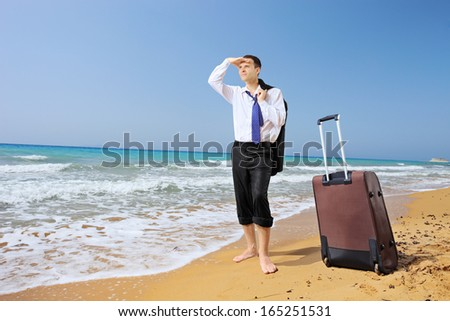 Full length portrait of a lost businessman with his luggage searching for way on a sandy beach - stock photo