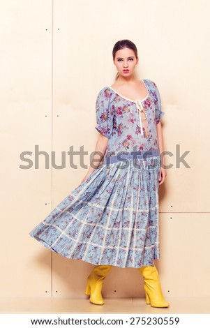 Full-length portrait of a lovely woman in romantic dress on wodden background - stock photo