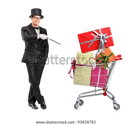 Full length portrait of a magician performing a trick on a shopping cart full of presents isolated on white background - stock photo